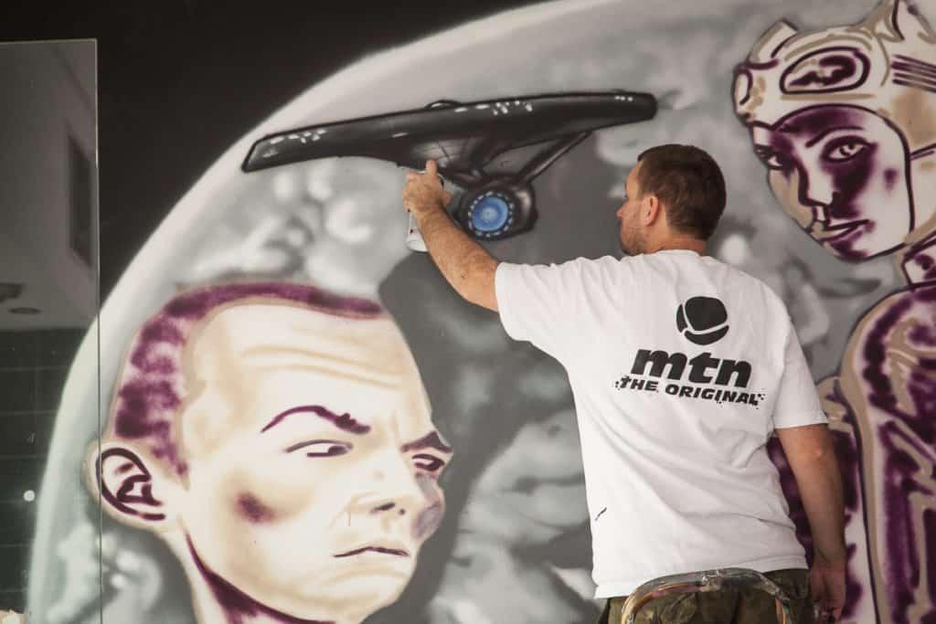 Graffiti artist painting mural